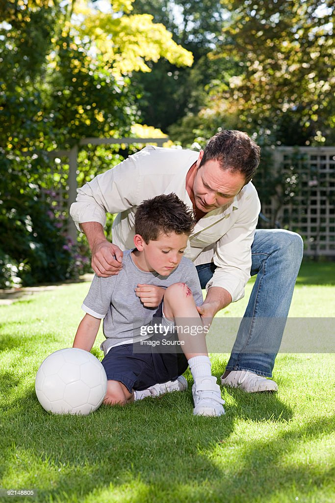 Father and son with a grazed knee : Stock Photo