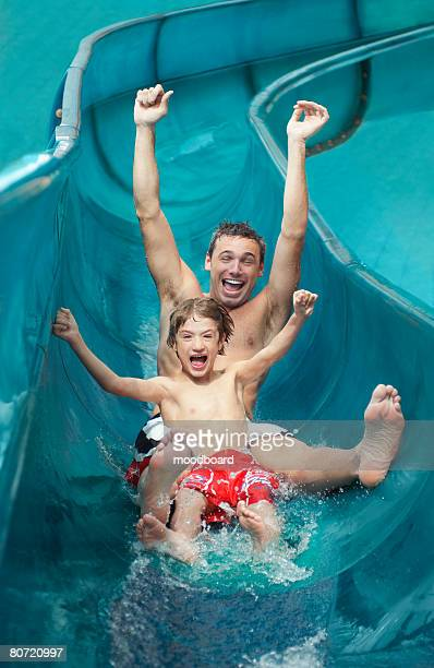 Father and son (7-9) with arms outstretched on water slide