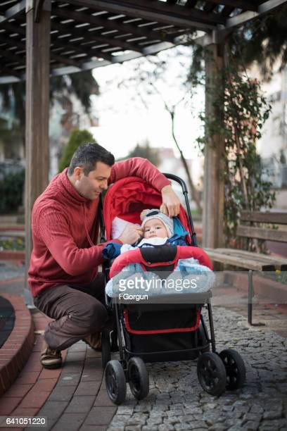 Father and son with baby stroller in park