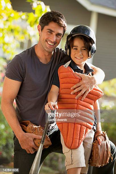 Father and son with baseball gear outdoors