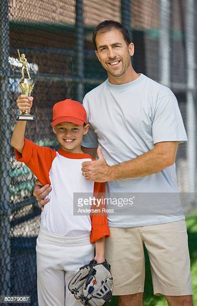Father and son with baseball trophy