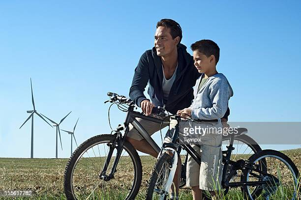 Father and son with bikes by a windfarm