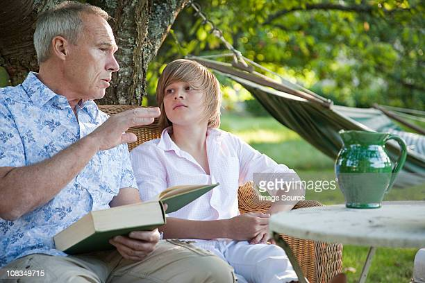 Father and son with book, in conversation