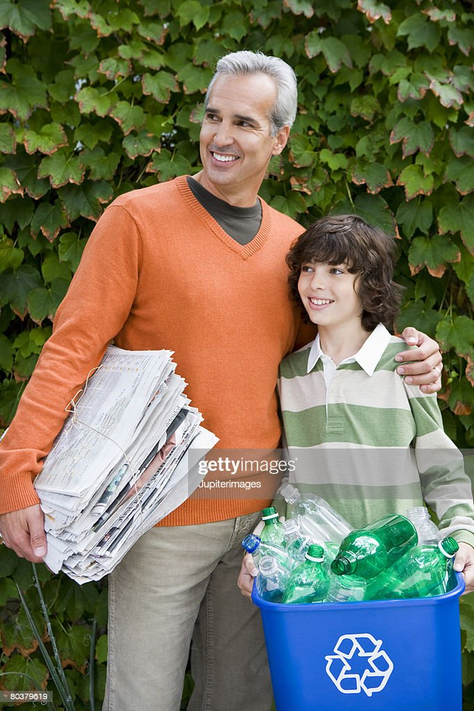 Father and son with bottle recycling bin and newspapers : Stock Photo
