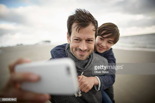 Father and son with cell phone on the beach
