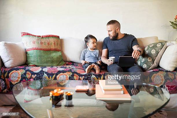 Father and son with digital tablets sitting on sofa at home