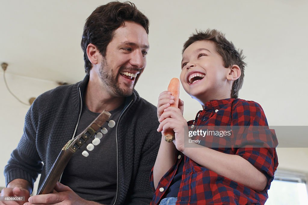 Father and son with guitar and carrot microphone