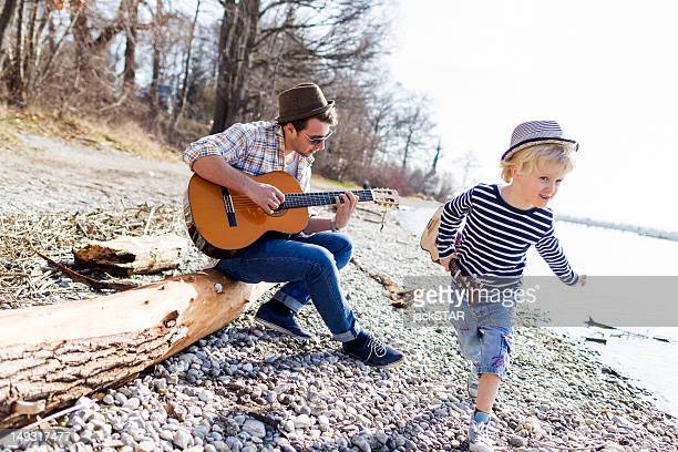 Father and son with guitars by creek
