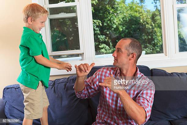 Father and son with hearing impairments signing play in American sign language on their couch