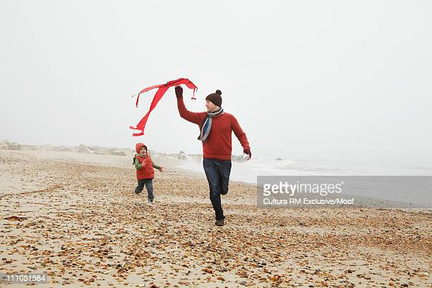 Father and son with kite at the beach