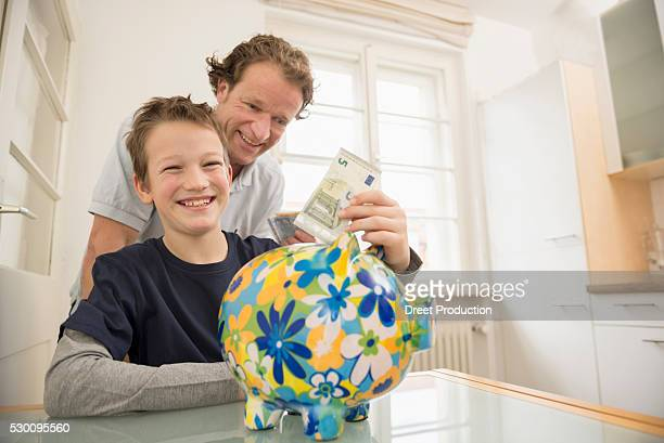 Father and son with piggy bank and 5 Euro note