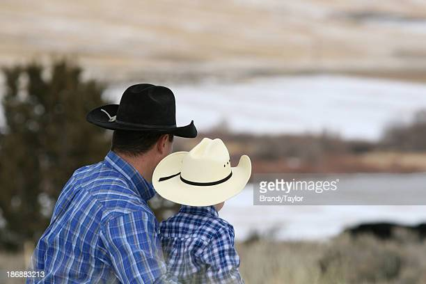 Father and son with plaid shirts and cowboy hats