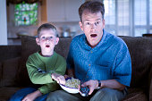 Father and son with remote control and popcorn