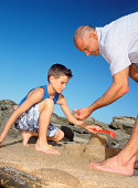 Father and son with sandcastle