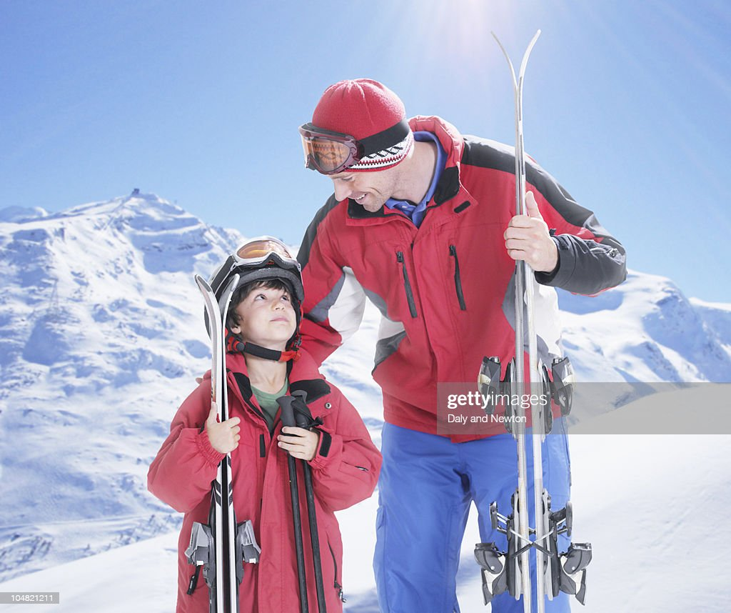 Father and son with skis on snowy mountain : Stock Photo