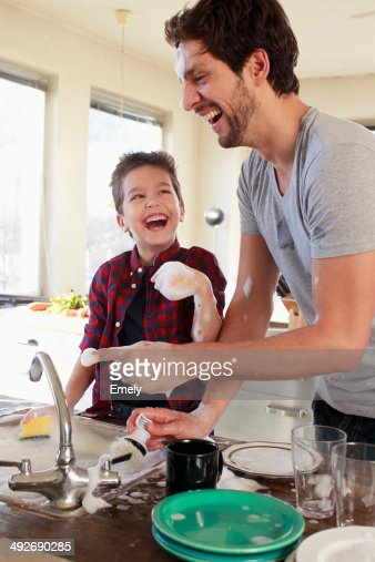 Father and son with soap suds on hands