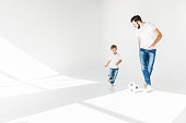 full length view of happy father and son playing with soccer ball on white