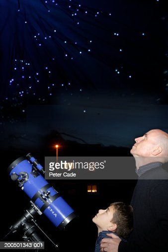 Father and son (9-11) with telescope looking at sky, night, side view : Stock Photo
