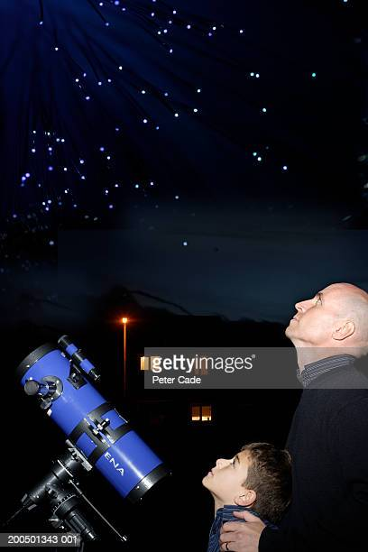 Father and son (9-11) with telescope looking at sky, night, side view