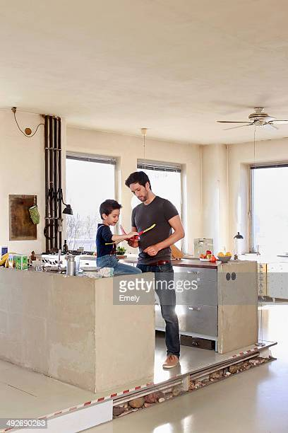 Father and son with toy airplane in kitchen