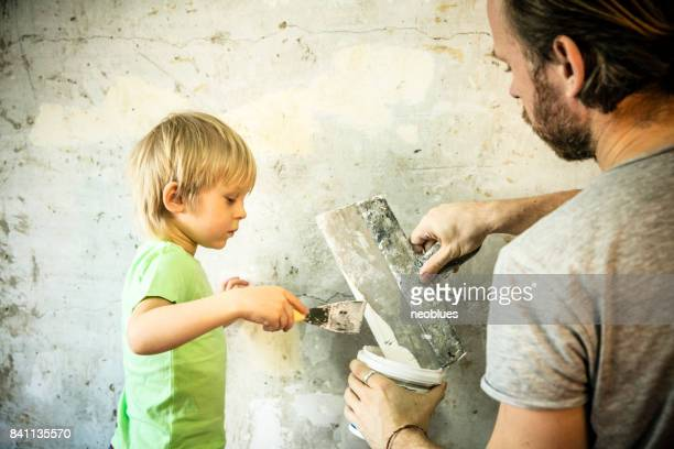 Father and son with trowel plastering a wall