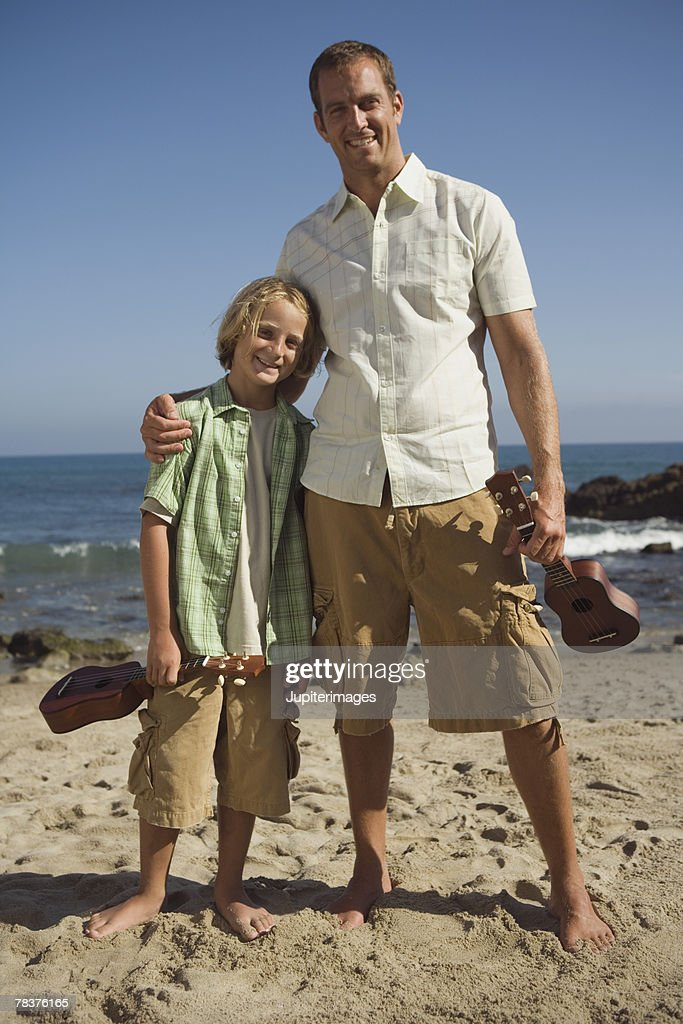 Father and son with ukuleles at the beach : Stock Photo