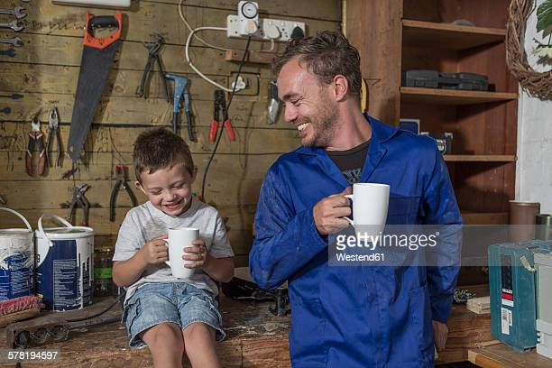 Father and son working in home garage having coffee break