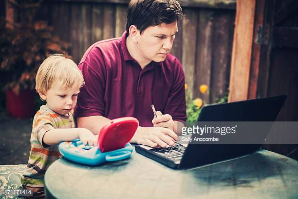 Father and son working on their laptops together