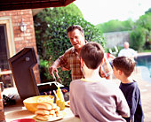 Father and sons barbecuing