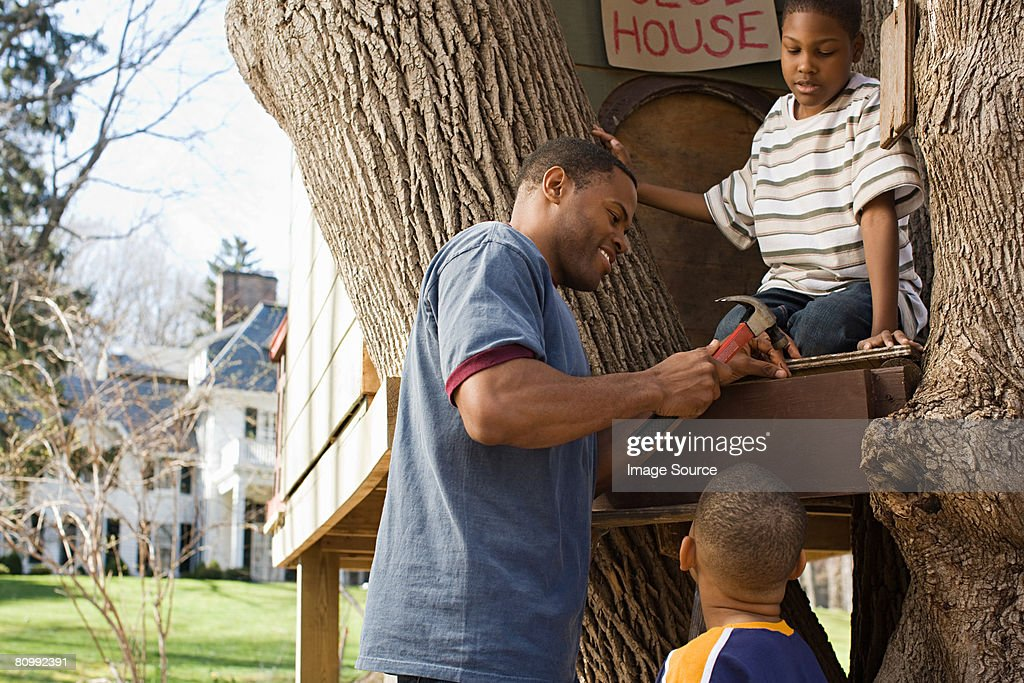 Father and sons building tree house : Stock Photo