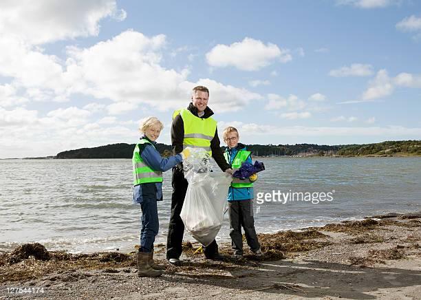 Père et fils, nettoyage de la plage