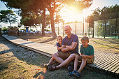 Father and sons hanging out in the park