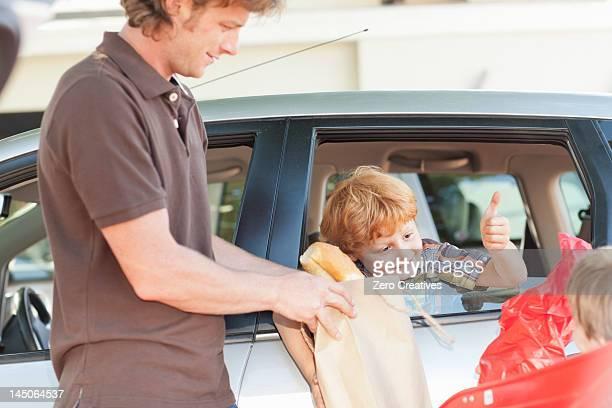 Vater und Söhne im Auto laden Lebensmittel