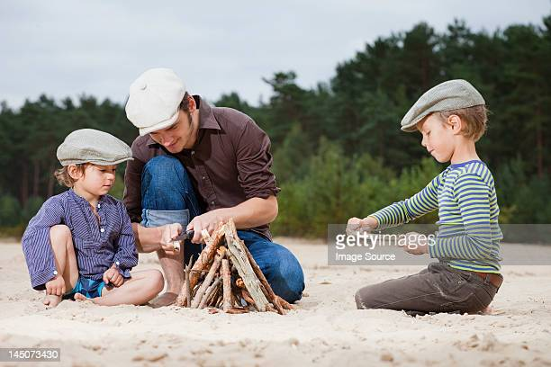 Father and sons making a bonfire on beach