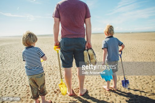 Father and sons on the beach together