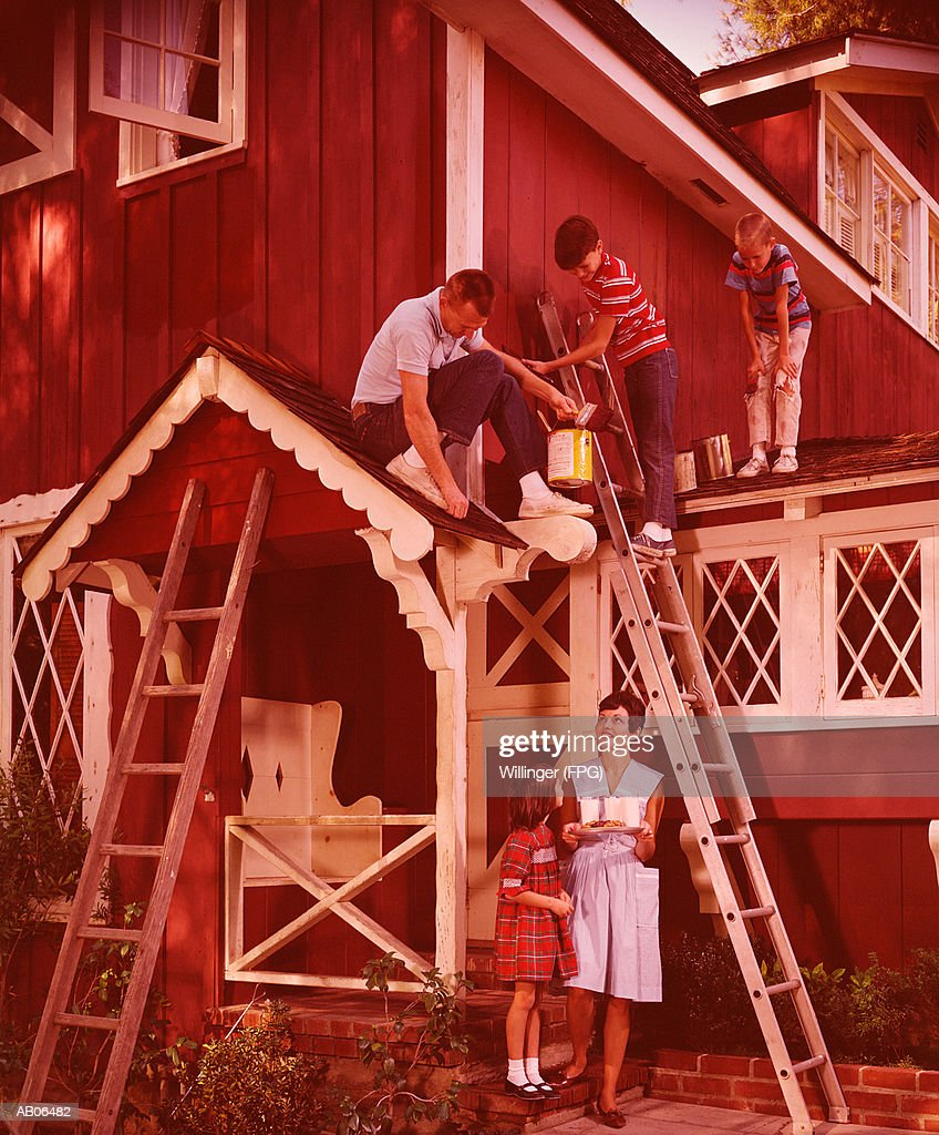 Father and sons painting house, mother and daughter bring snacks : Stock Photo