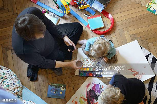 Father and sons painting on floor
