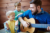 Young man playing guitar with two sons near by