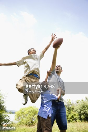 Father and Sons Playing Football : Stock Photo