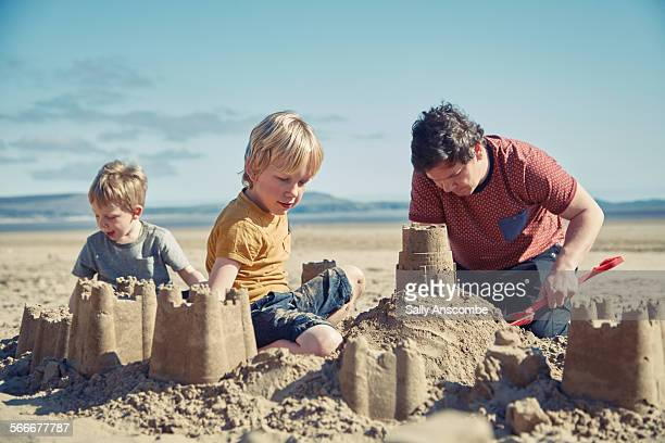 Father and sons playing on the beach