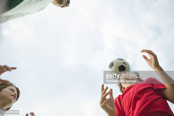Father and sons playing soccer, low angle view