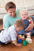 Father And Sons Playing With Coloured Blocks At Home
