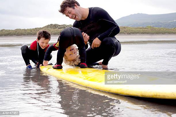 Father and sons playing with surfboard