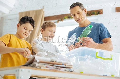 Father and sons preparing plastic bottles for recycling : Stock Photo