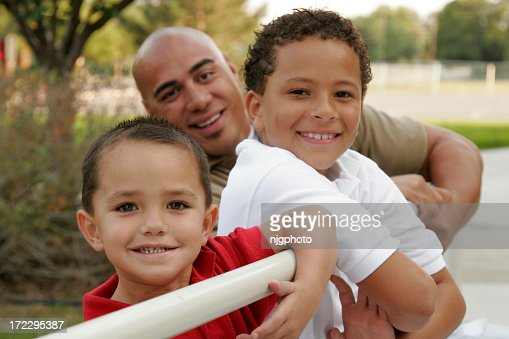 Father and sons smiling and leaning against white railings