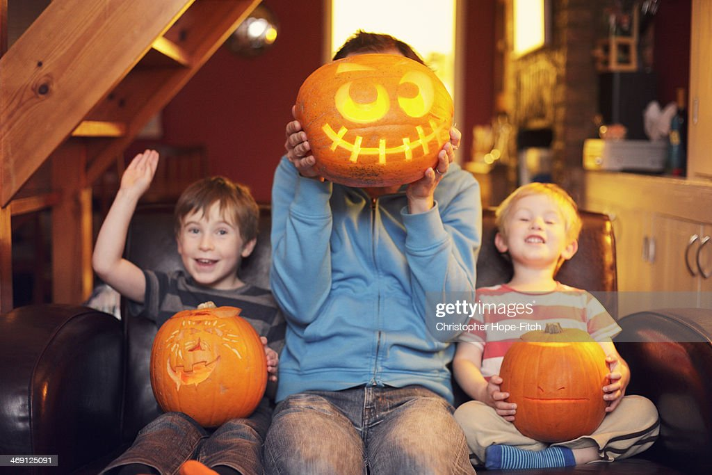Father and sons with carved pumpkins : Stock Photo