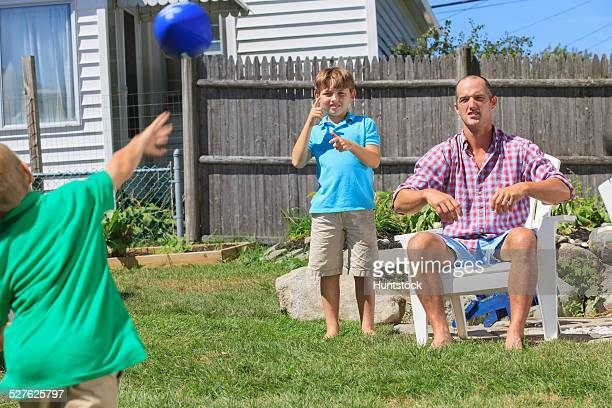 Father and sons with hearing impairments playing football and signing brother in American sign language in backyard