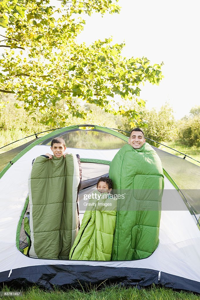 Father and Sons Wrapped in Sleeping Bags In Tent : Stock Photo