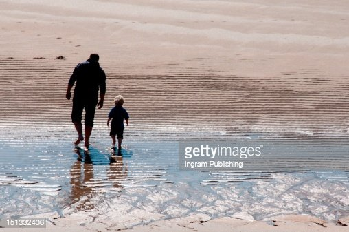 Father and sun walking on the sand in the sunshine. : Stock Photo
