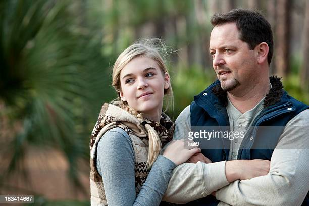 Father and teenage daughter outdoors